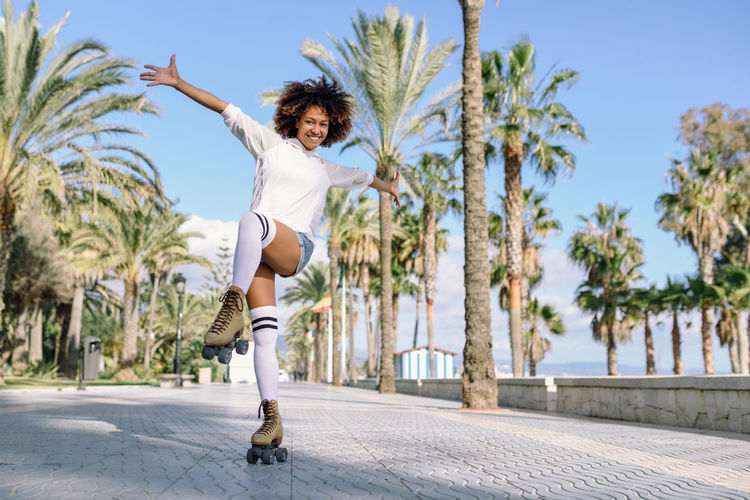 Smiling black woman on roller skates riding outdoors on beach promenade with palm trees. Smiling girl with afro hairstyle rollerblading on sunny day. Afro Afrohair Arms Raised Beautiful Woman Casual Clothing Curly Hair Enjoyment Full Length Fun Hair Hairstyle Happiness Healthy Lifestyle Leisure Activity Lifestyles Motion One Person Outdoors Real People Roller Skate Roller Skating Rollerblading Women Young Adult Young Women