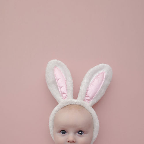 Portrait of cute baby against pink background