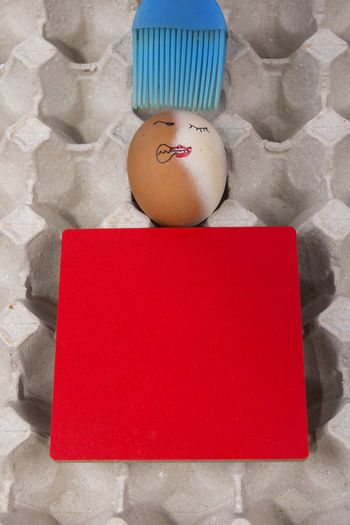 Cartoon face expression at egg and red board with finger also plastic brush Angry; Blue Brush; Blue Plastic Brush; Brush; Close-up Confuse; Egg Egg Carton Excited; Expression; Food Food And Drink Indoors  Joke; No People Plastic; Sad; Scare; Shy; Sick
