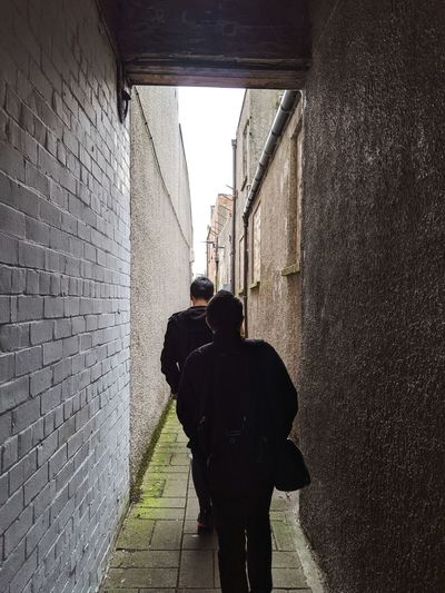 Rear view of people walking on alley amidst buildings