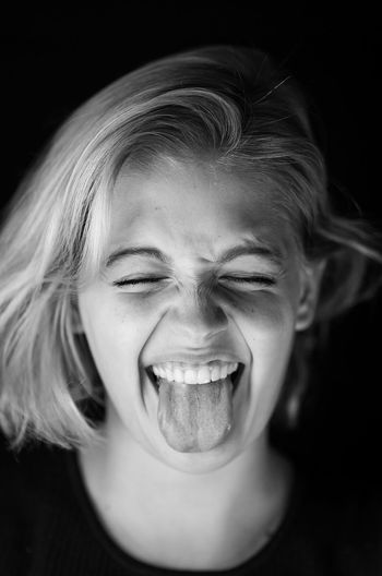 Close-up of young woman with eyes closed sticking out tongue against black background
