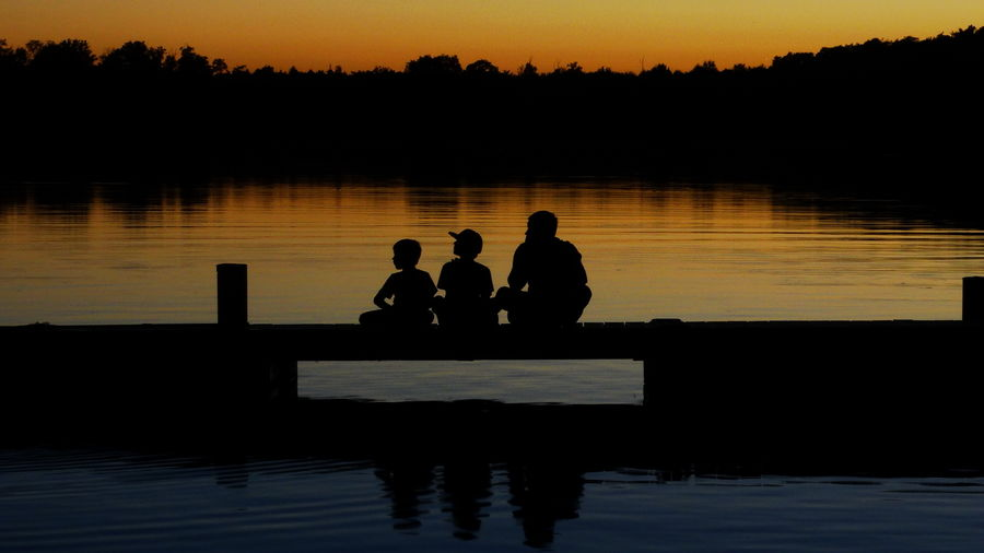 Rear View Of Silhouette Father With Sons O Pier Over Lake During Sunset