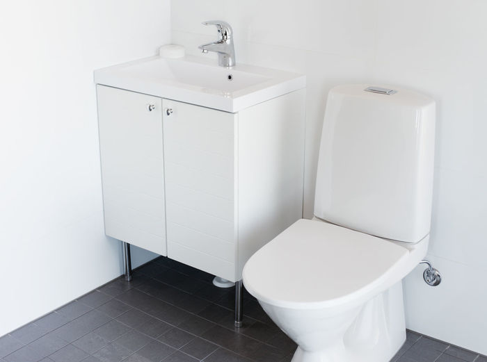 High angle view of toilet bowl by cabinet in bathroom