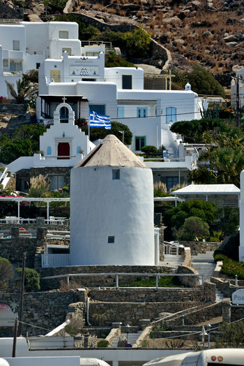 view of a white windmill in Mykonos with greek flag surrounded by buildings Architecture Building Exterior Built Structure Building Day City Nature No People Tree Outdoors High Angle View Spirituality Sunlight Residential District Travel Destinations Land Windmill Greek Windmill Greek Greek Flag Mykonos,Greece Chora City Cityscape Greek Architecture Highlights Tourism White Building