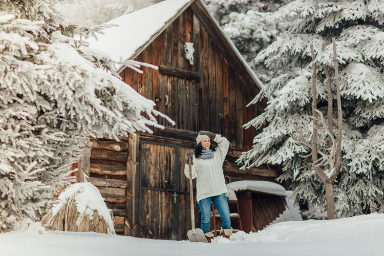 Smiling young woman standing on snow field against cottage