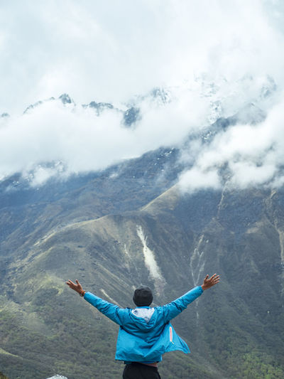 Rear view of man with arms outstretched standing on mountain against cloudy sky