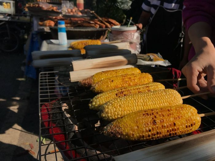 Street Foods Food And Drink Food Freshness Real People For Sale Corn Food Stories Corn On The Cob Preparing Food Healthy Eating Barbecue Market Preparation  Close-up One Person Ready-to-eat Human Hand Summer Exploratorium