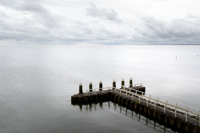Noord Holland Pier At The Lake Beauty In Nature Cloud - Sky Day Groyne Horizon Horizon Over Water Ijsselmeer Jetty Lake Nature No People Outdoors Pier Scenics - Nature Sea Sky Tranquil Scene Tranquility Water Waterfront Wood - Material Wooden Post