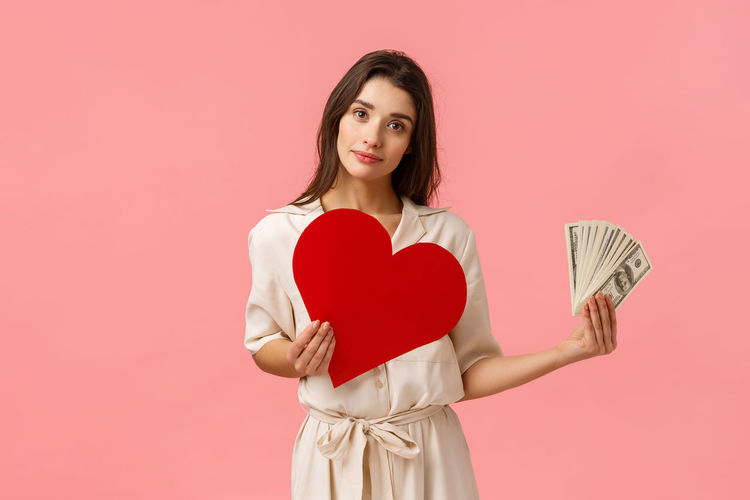 Portrait of woman holding heart shape against red background
