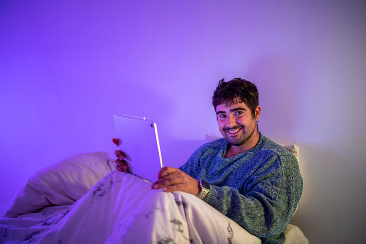 Portrait of man using digital tablet sitting on bed against wall at home