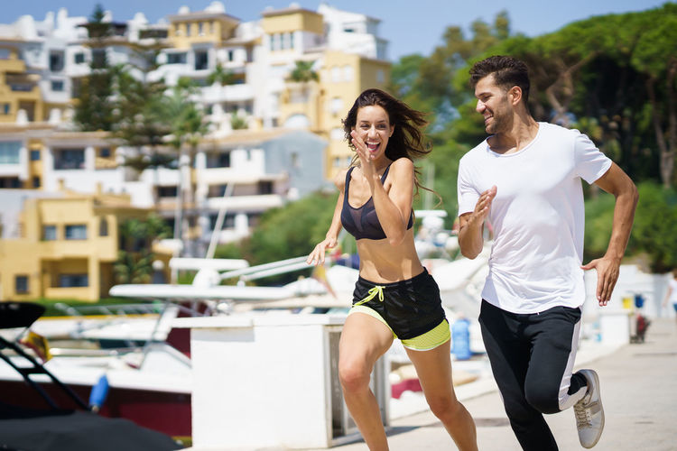Couple running on footpath against buildings in city