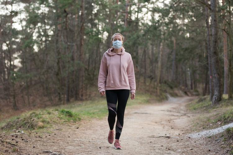 Full length of woman wearing mask walking at park