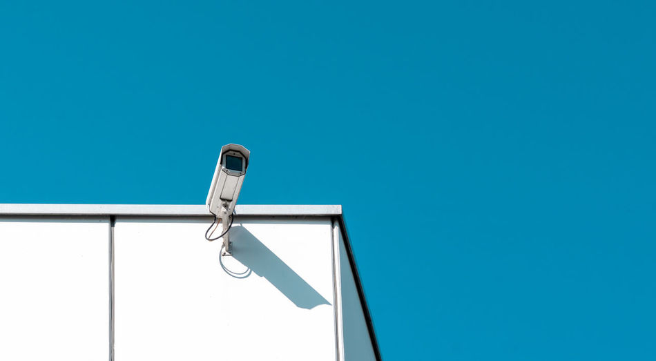 Low angle view of security camera on wall against clear blue sky