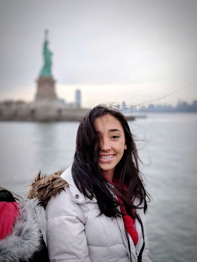 Portrait of smiling woman sitting against statue of liberty