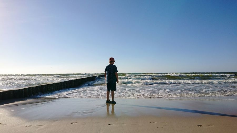 Rear view of boy standing on shore against blue sky