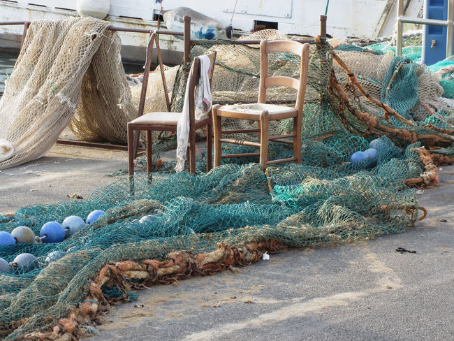 Weathered fishing nets on a traditional harbor pier in Livorno, Tuscany, Italy Catcher Coast Day Equipment Fish Fisherman Fishing Fishing-gear Fishnets Harbor Hunting Lift Livorno Mesh Nets Nobody Objects Outdoors Pier Relax Rope Sea Shore Tool Tuscany