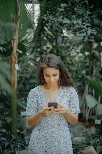 Young woman holding smart phone while standing by plants