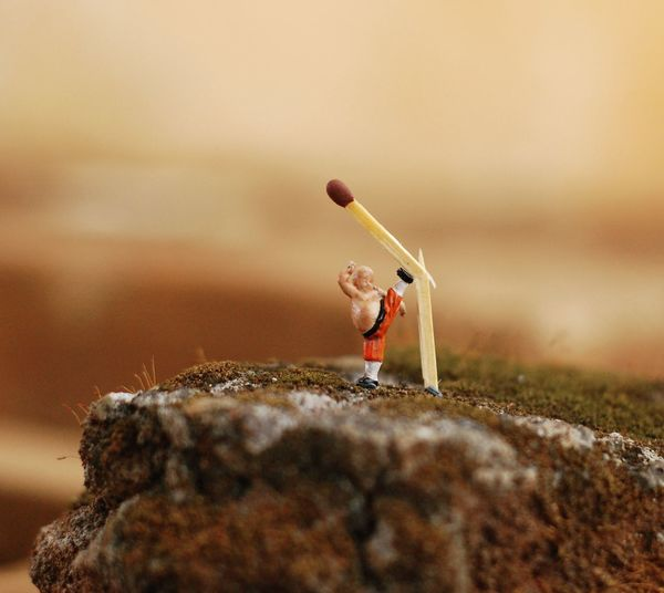 Optical illusion of toy breaking matchstick on rock