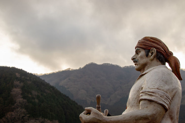 Side view of statue against mountain range against sky