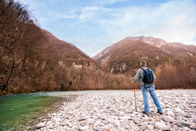 Rearview Of Male Hiker Standing By Stream Against Mountains