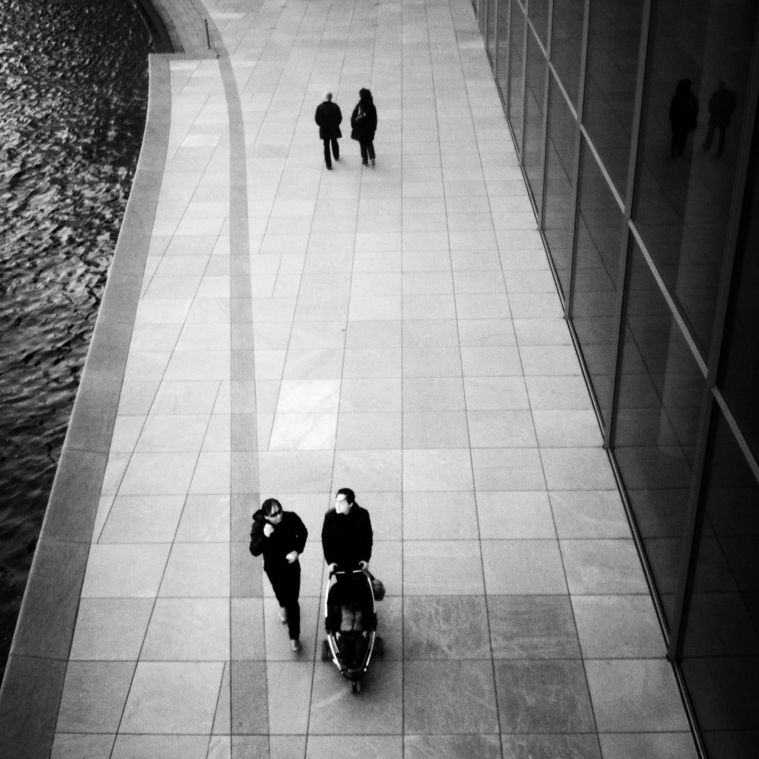 indoors, men, lifestyles, tiled floor, walking, full length, person, leisure activity, rear view, flooring, high angle view, shadow, togetherness, sunlight, the way forward, unrecognizable person