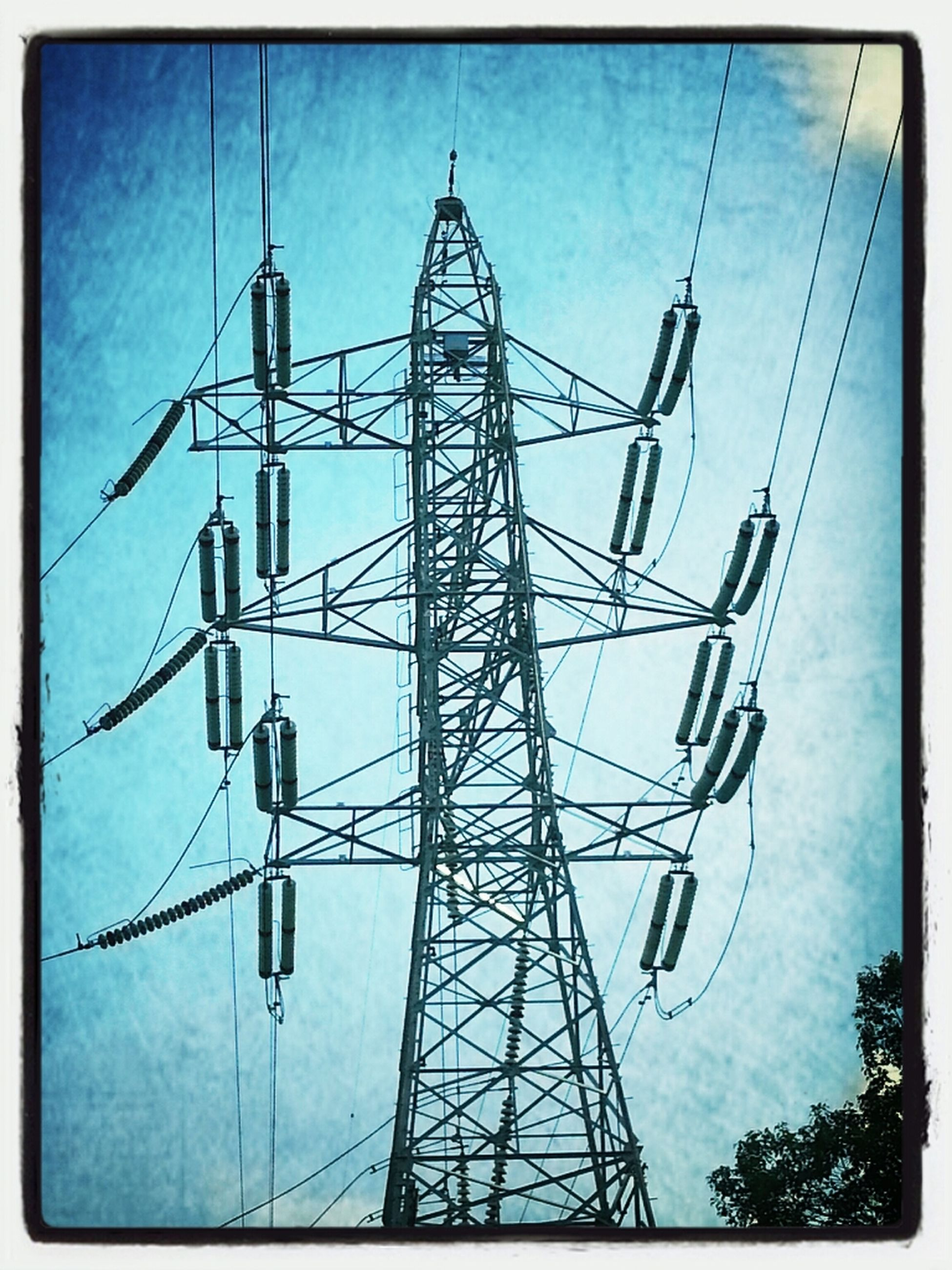 low angle view, transfer print, auto post production filter, electricity, sky, electricity pylon, technology, power supply, blue, power line, connection, fuel and power generation, metal, day, outdoors, built structure, no people, tall - high, lighting equipment, silhouette