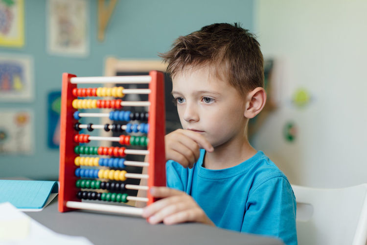 Portrait of boy using abacus