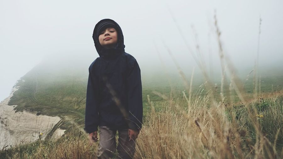 Young boy standing on clifftop against sky