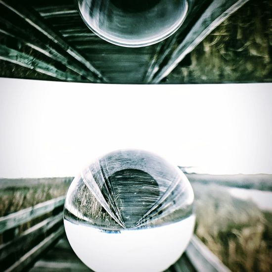 Close-up of crystal ball on glass against blurred background