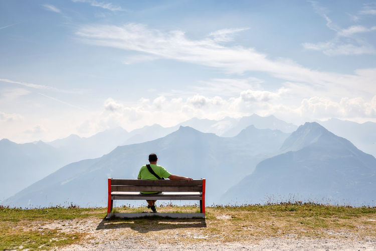 A man sits on a wooden bench at the top of the Alps and looks at the beautiful mountain landscape. Mountains Mountain Peak Clouds And Sky Alps Alpine Landscape Alpine Mountain Scenics - Nature Nature Outdoors Wooden Bench Relax Sitting Man Children Teenager Woman One Person Rear View Seat Beauty In Nature Mountain Range Tranquility Sky Tranquil Scene Real People Men Day Full Length Lifestyles Leisure Activity Idyllic Looking At View
