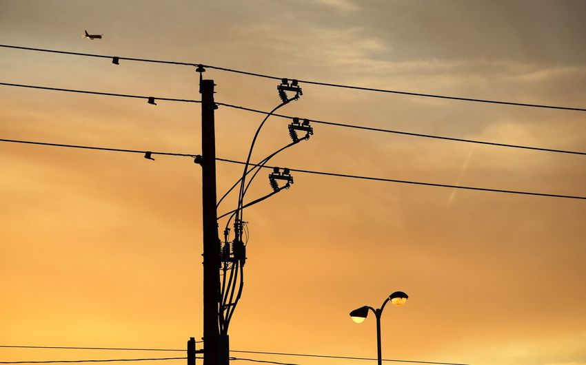 American Lines Curved Pattern Electricity Pylon Gestures Lights Against Sky Low Angle View Plane Approach Sunset Sillhouettes Telegraph Pole Telephone Line