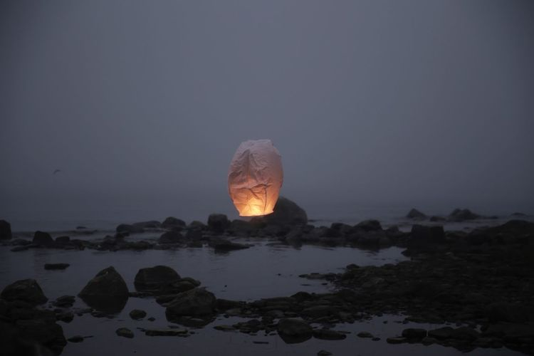 Paper lantern flying over rocks at beach against sky during dusk