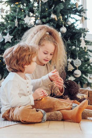 Full length of girl sitting in christmas tree