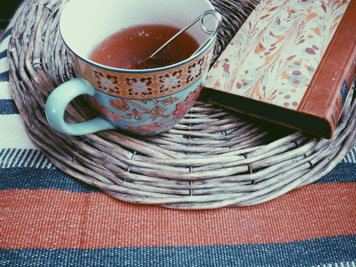 High angle view of strainer in black tea by book on wicker