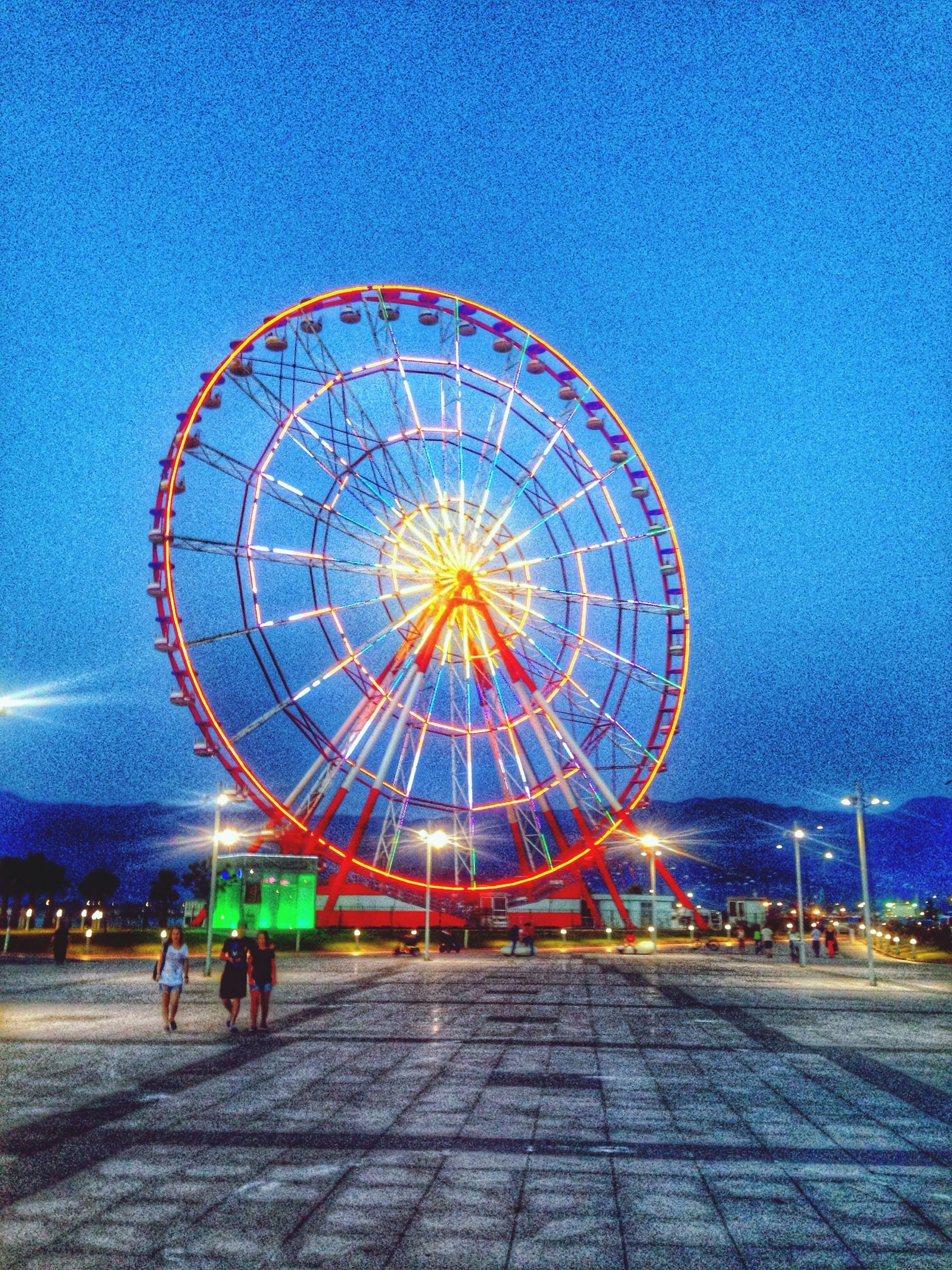 illuminated, leisure activity, sky, night, lifestyles, amusement park, arts culture and entertainment, ferris wheel, men, amusement park ride, blue, dusk, street, clear sky, person, road, lighting equipment, incidental people, outdoors