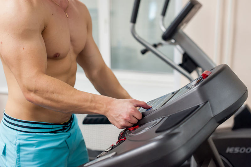Shirtless young man on treadmill in gym