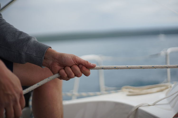 Midsection of man holding rope on boat