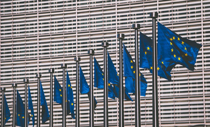 Low angle view of european union flags against modern building