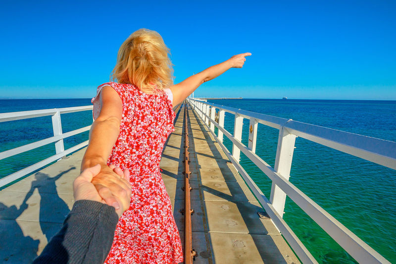 Follow me, blonde woman holding hands at Busselton jetty in Busselton, Western Australia. Concept of the journey of woman tourist traveler, holding man by hand over iconic wooden pier in WA, Australia Steam Train Train Australia Jetty Busselton Busselton Jetty Busselton Western Australia Busseltonjetty Western Australia Beach Station Travel Pier Tourist Railway Railway Track Sea Tourist Attraction  Landmark Woman Girl Followme Follow Me Walking Water Railing Sky Horizon Over Water Leisure Activity One Person Horizon Blue Nature Real People Lifestyles Hair Beauty In Nature Rear View Blond Hair Scenics - Nature Three Quarter Length Day Looking At View Outdoors Hairstyle