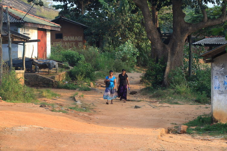 Two Women Walking On Country Road