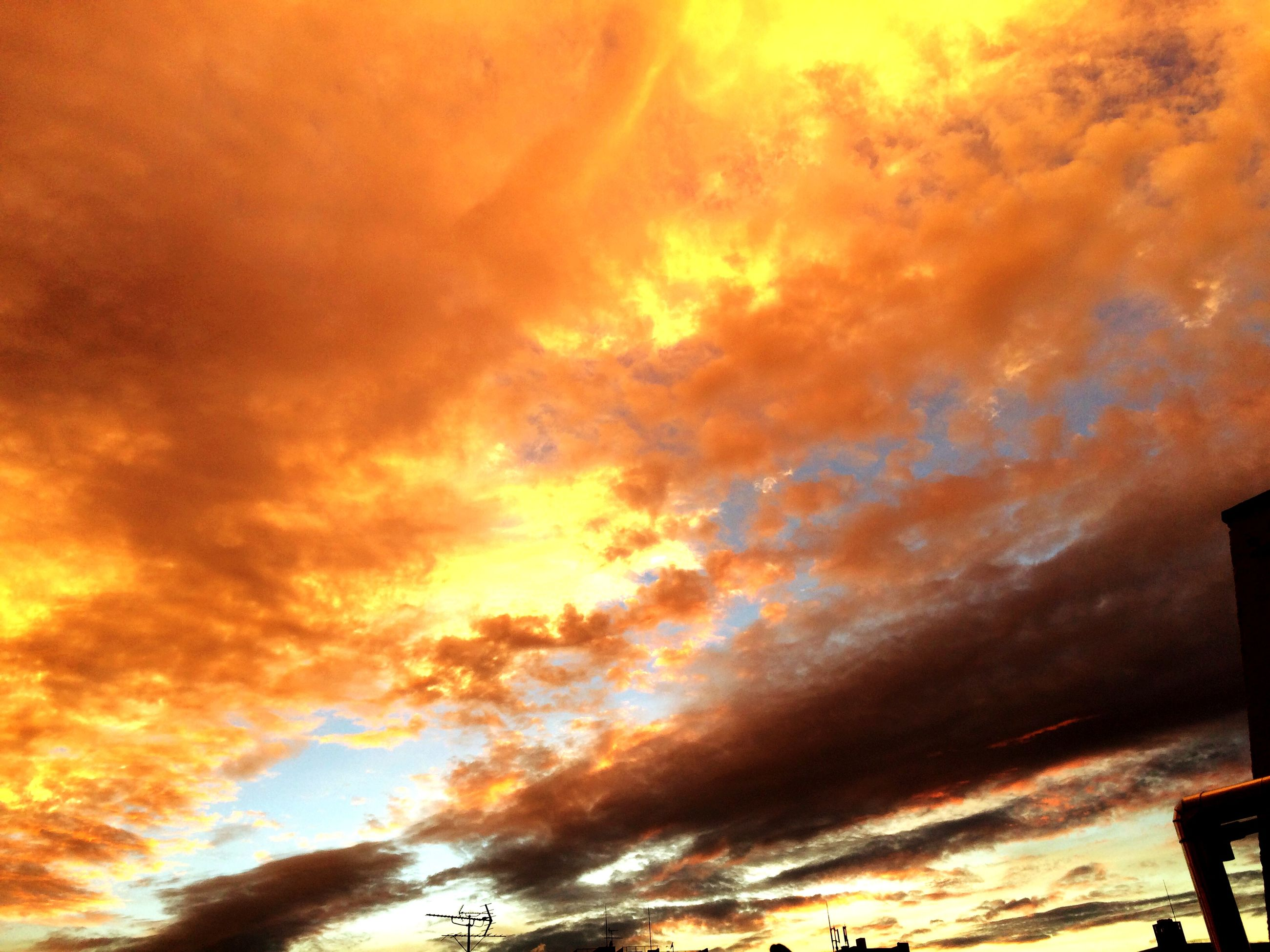 low angle view, sunset, sky, cloud - sky, orange color, cloudy, dramatic sky, beauty in nature, silhouette, scenics, cloud, tranquility, nature, idyllic, outdoors, built structure, tranquil scene, no people, weather, architecture