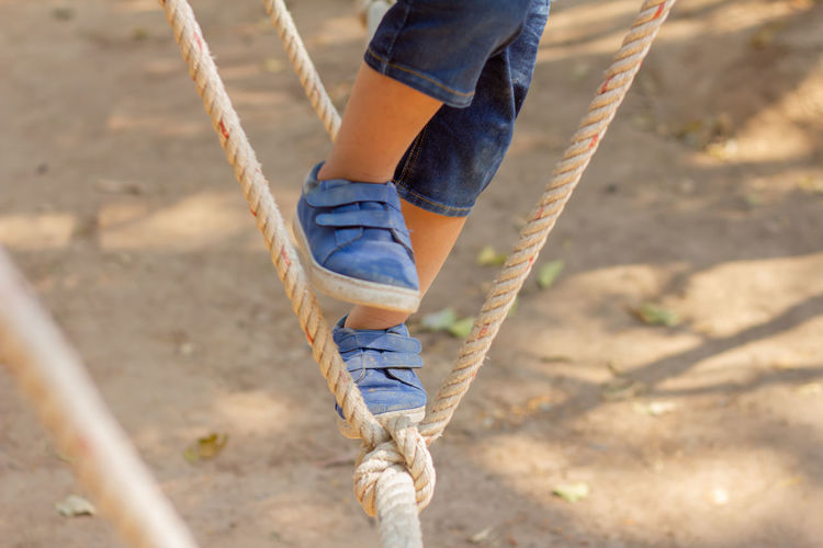 One Person Low Section Day Real People Leisure Activity Human Body Part Rope Lifestyles Playground Strength Human Leg Body Part Casual Clothing Nature Focus On Foreground Climbing Outdoors Balance Swing Jeans Outdoor Play Equipment