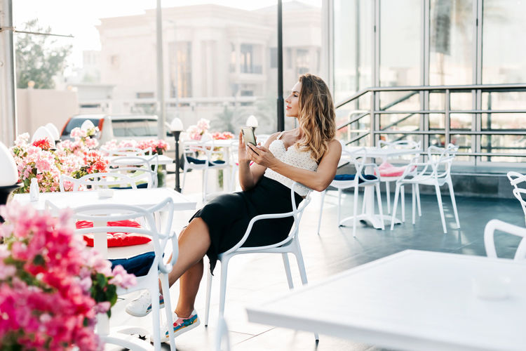 An attractive woman sits in a street cafe and uses her phone to exchange messages