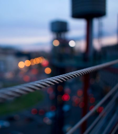 Close-up of illuminated lighting equipment on railing in city