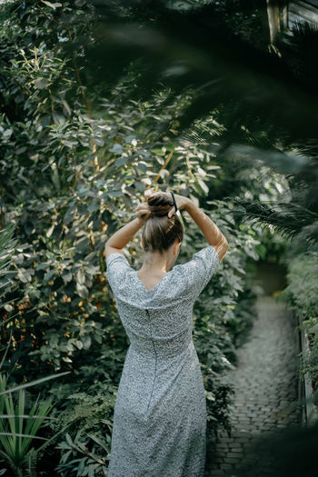 Rear view of woman standing by plants