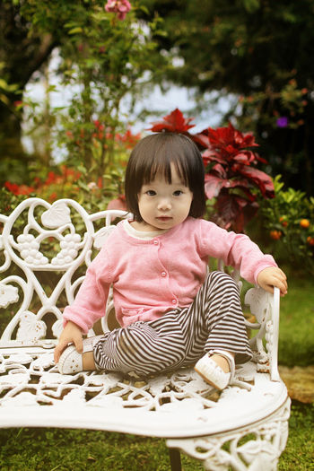 Cute little Asian girl sitting on the bench in the garden Childhood Child One Person Innocence Cute Plant Real People Portrait Casual Clothing Full Length Day Looking At Camera Sitting Nature Babyhood Front View Grass Flower Outdoors Bangs Asian Girl Bench Gardern The Portraitist - 2019 EyeEm Awards