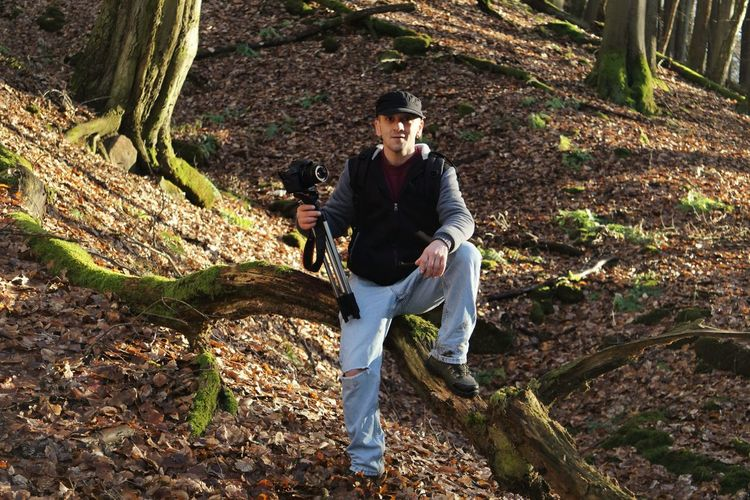 Portrait of man with tripod and camera in forest