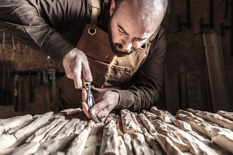 Man carving wood on table at workshop