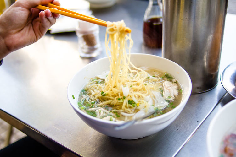 Cropped image of person eating noodles from chopsticks at restaurant