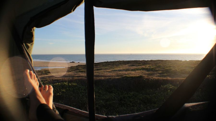 Low section of person relaxing in tent at beach against sky